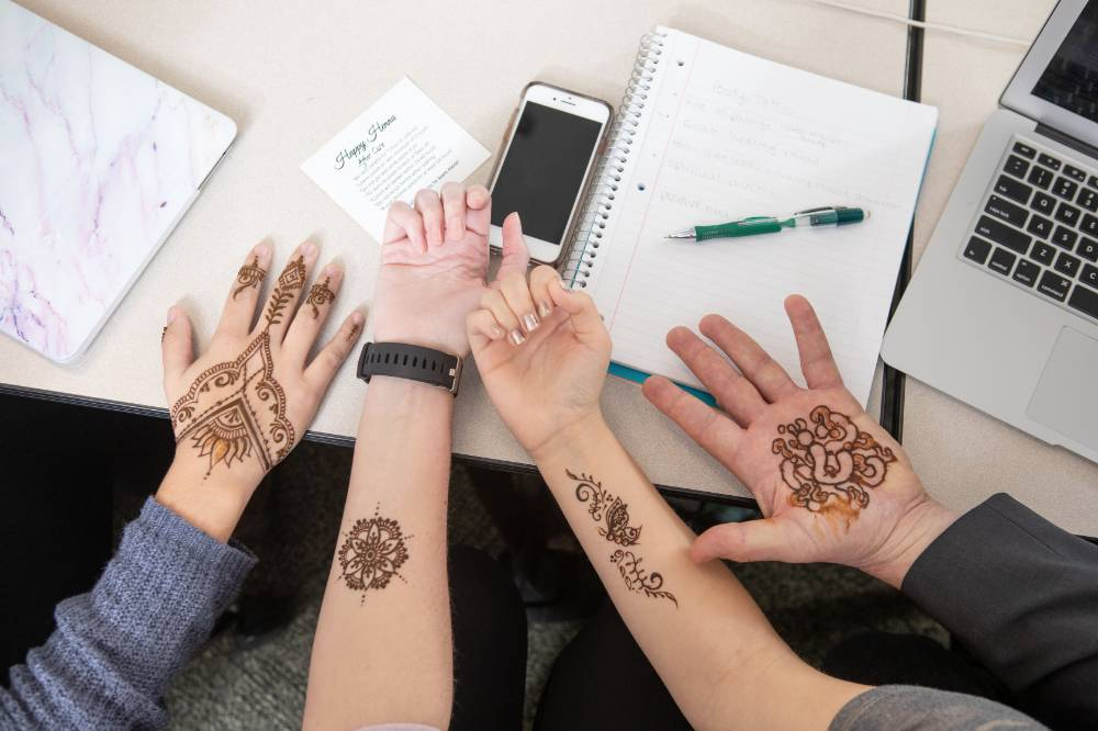 Students display their henna tattoos.